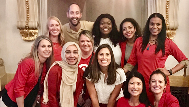 Kiera and 10 Target team members dressed in red and khaki stand together smiling at an event