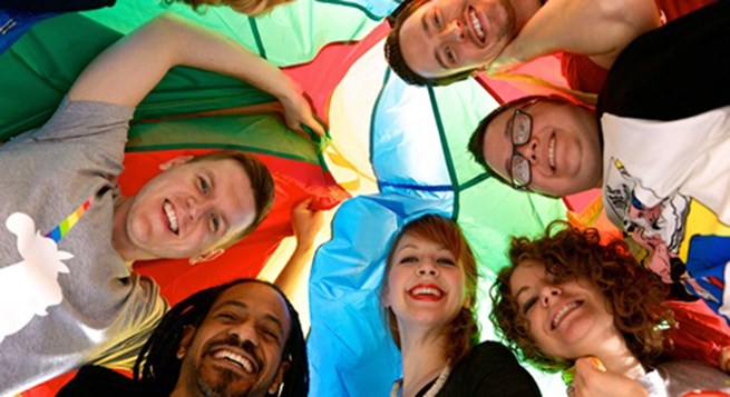 Six members of our LGBTA Business Council pose in a circle under a parachute.