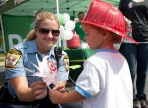 police officer gives a child a pinwheel