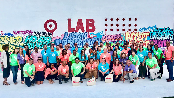 thirty team members in colorful Target shirts pose in front of graffiti wall