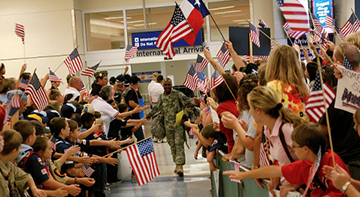 team members greet soldiers at a welcome home event