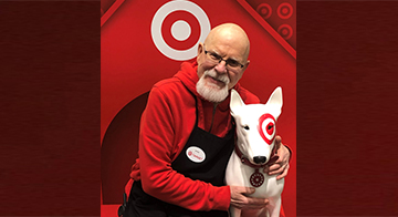 Vyto sits with his arms around a statue of Target's mascot, Bullseye the dog