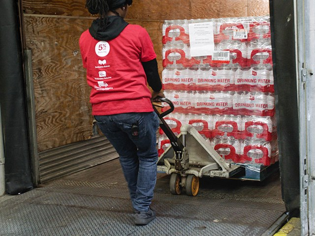 team member in red t-shirt pulls a pallet of bottled water