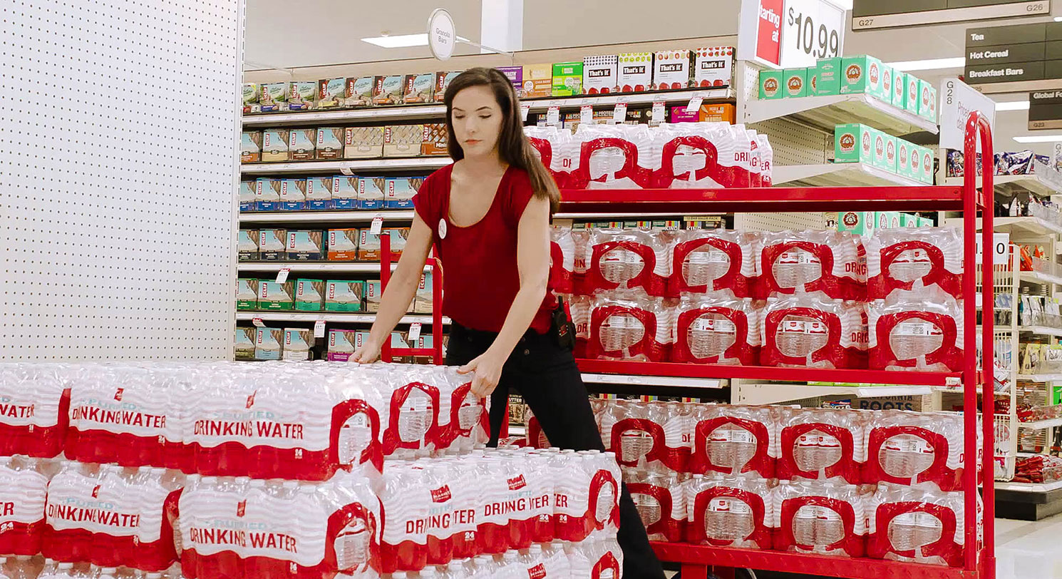Female team member stocking an end cap with packages of Market Pantry bottled water
