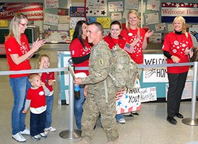 team members welcome a returning soldier home
