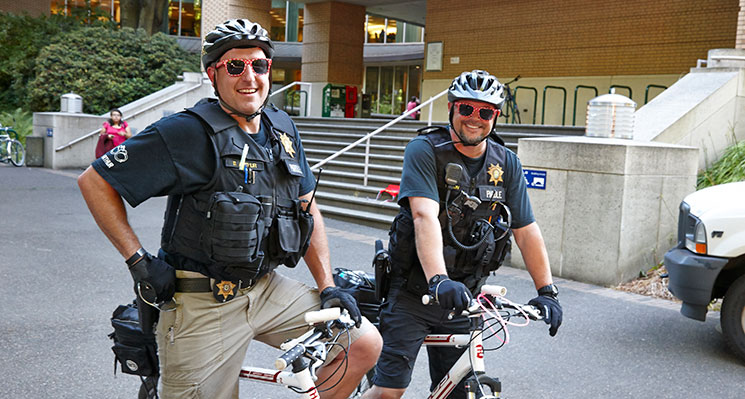 two police officers on bikes with helmets and Target sunglasses