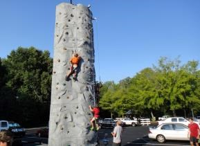 kids climb a rock wall at the Roswell, Ga., NNO event