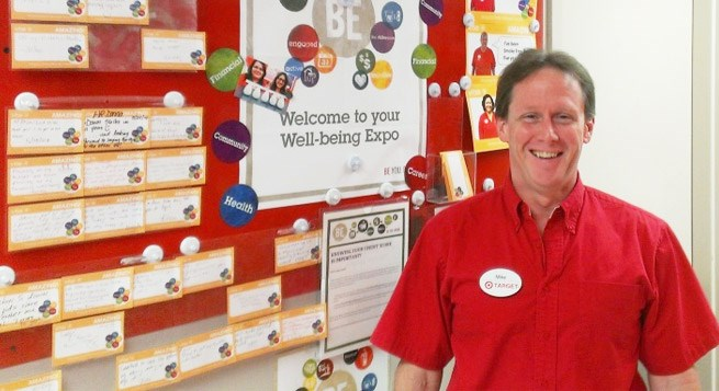 Michael Ayers stands in his Target store near the Well-being Expo board.