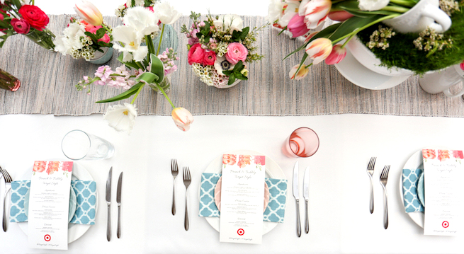 Flower arrangement over blue and grey tablerunner with pink orange and blue table settings
