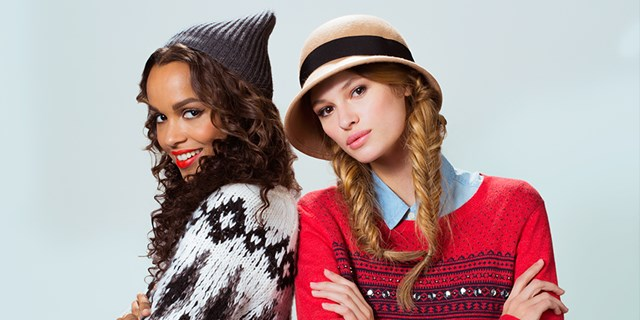 Two models wearing patterned sweaters and hats