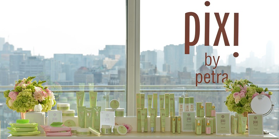 Pixi by petra spring collection products on a table in front of a cityscape window view