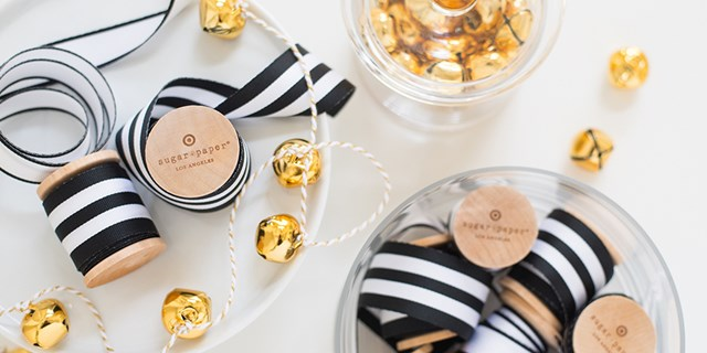 black and white Sugar Paper ribbon spools and gold bells on gold and white string