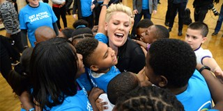 Artist P!nk hugs a group of children at the UNICEF Powerband event in Harlem