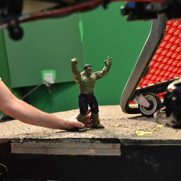 Behind the scenes photo of an animator holding the Hulk action figure