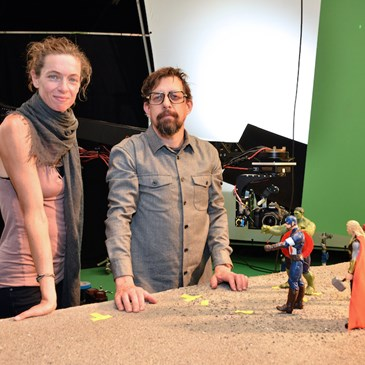Behind the scenes photo of the co-directors in front of the posed Avengers action figures