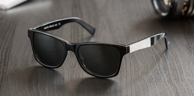 Black sunglasses rest atop a black wooden table