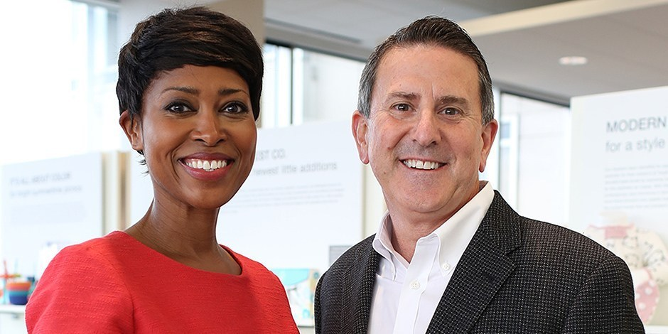 Laysha Ward and Brian Cornell stand in front of shelves filled with colorful Target products