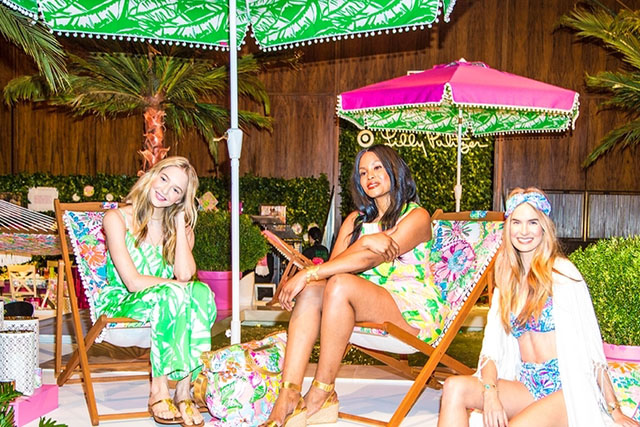Three models wearing Lilly Pulitzer apparel sit on colorful deck chairs under umbrellas.