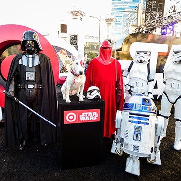 white terrier dog with red bullseye over eye poses with Star Wars characters including Darth Vader