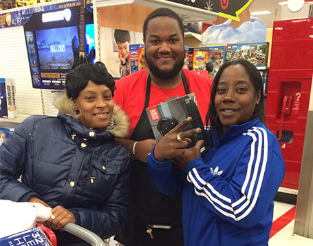 An Electronics team member with two smiling guests who just found a great deal