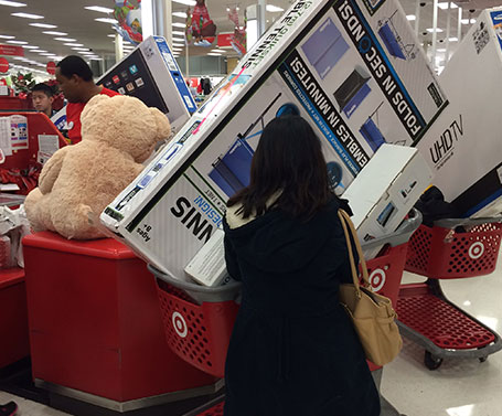A woman waiting in the checkout line with two carts full of Black Friday deals