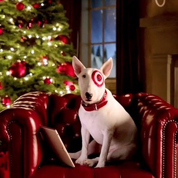 white terrier dog with red bullseye around his eye sits in a red armchair in front of a fire