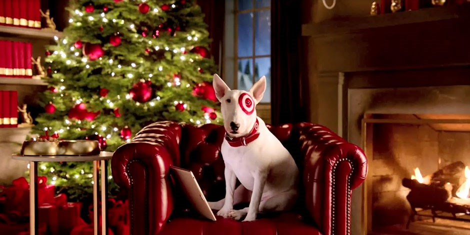 Target's Bullseye dog mascot sitting in front of a Christmas tree and fireplace