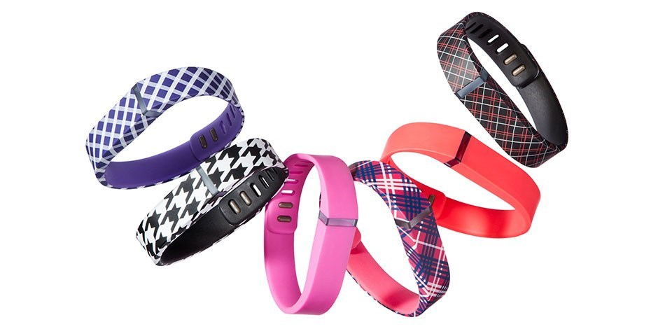 A group of six Fitbit wristband devices with a range of colorful patterns