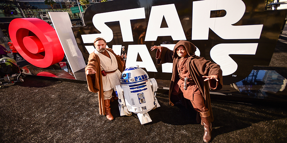 Two Jedi Knights pose with R2D2 in front of the event sign