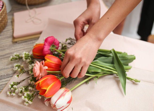 Woman wrapping bouquet of orange and pink flowers