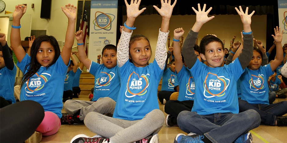 Los Angeles students sitting on the floor raise their hands high during a Kid Power activity.
