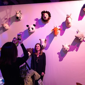 Woman taking a picture in front of Pillowfort animal wall
