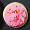 A banana, pink-frosted cookie and orange