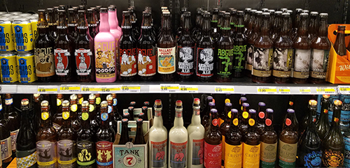 Two shelves filled with colorfully labeled bottles of craft beer.