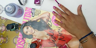 Woman painting her nails pink on top of Cosmopolitan magazine