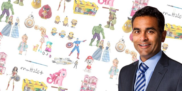 Nik Nayar stands in front of a background featuring several popular toy brands