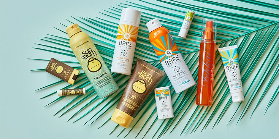 various brands of sunscreen over palm leaf on green background
