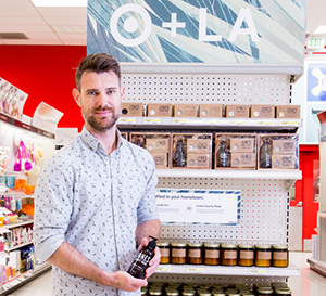 Ryan Rogers stands in front of a shelf of his products.
