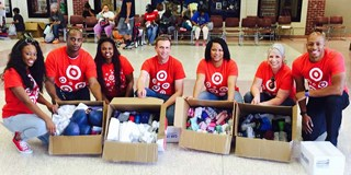 Seven Target volunteers pack boxes of flood relief supplies.