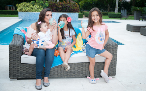 Barbara and her three daughters sip lemonade on a couch