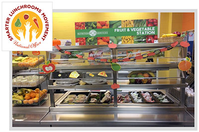 A school cafeteria counter with healthy foods next to the Smarter Lunchrooms Movement logo
