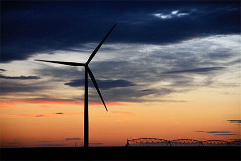 A wind turbine in front of a sunset