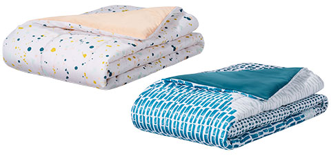 A white paint-splattered bed spread and a white bed spread with teal print