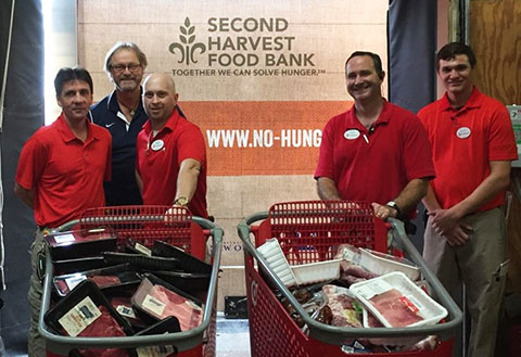 Five team members donate carts of food to the Second Harvest Food Bank