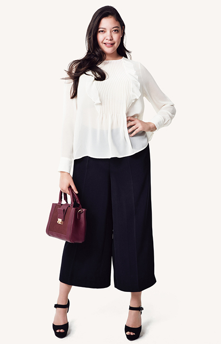 Model in white blouse and black coulotte pants