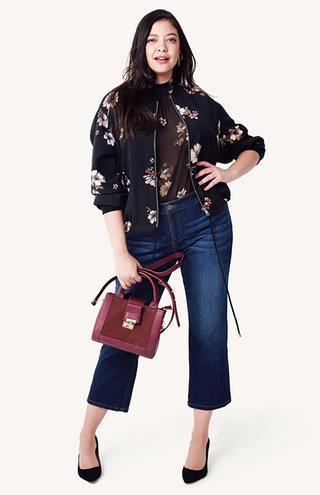 A model in a brown top, jeans and a floral jacket