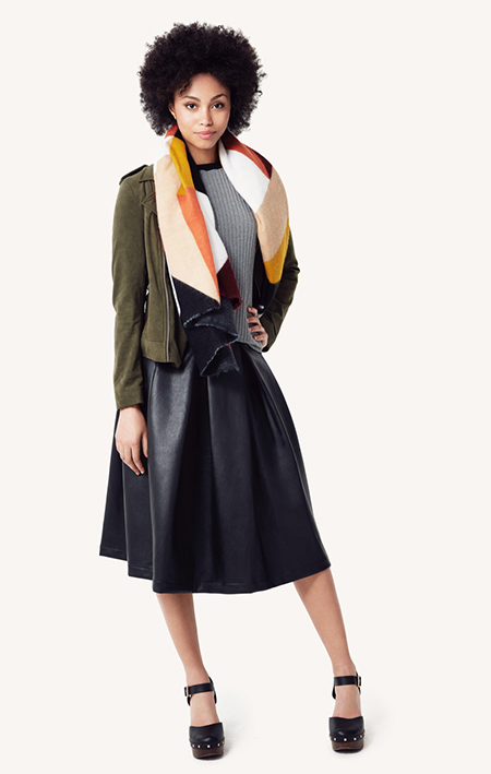 A model in a grey dress, green jacket and color block scarf