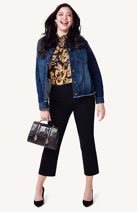 A model in a jean jacket, yellow floral top and black cropped pants