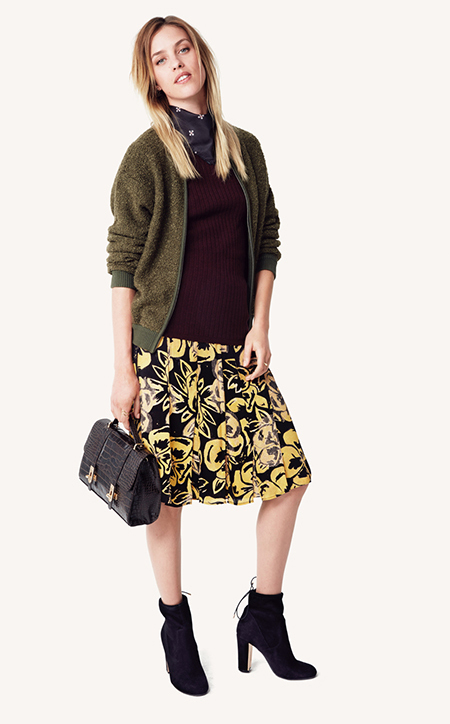 A model in a wine-colored top, green jacket, floral skirt and neck scarf
