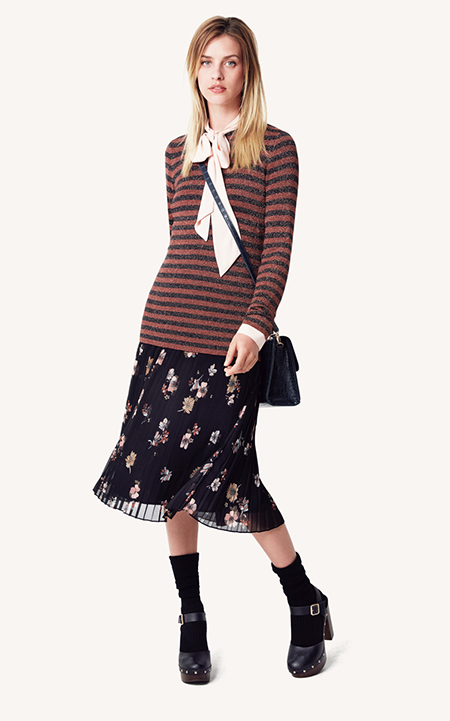 A model in a mod stripe top, pink neck scarf and floral skirt